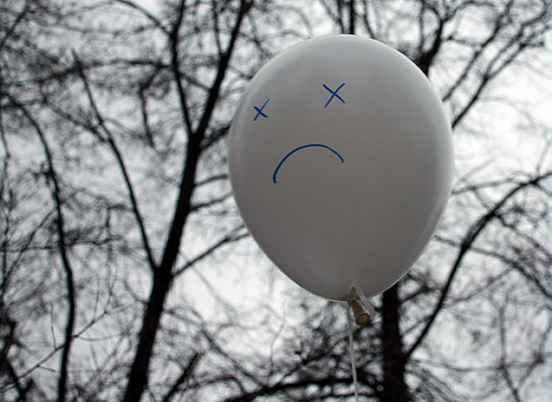Фото: белый воздушный шар с грустным смайликом