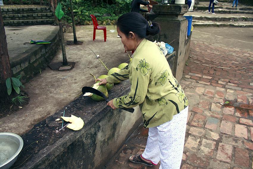 Вьетнамская женщина вскрывает кокосовый орех