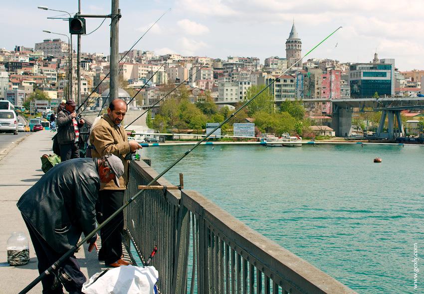 Рыбаки на мосту ловят рыбу